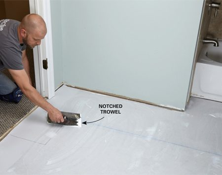 <b>Photo 5: Spread the adhesive</b></br> <p>Spread the adhesive with a small notched trowel. Cover every inch, and don't leave puddles. Start at the end of the room and work your way toward the door.</p>