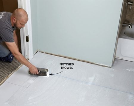 Spread the adhesive first before laying the luxury vinyl tiles.