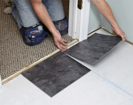 <b>Photo 7: Slide tiles under trim</b></br> <p>Once a tile is laid flat on the glue, it's stuck. In order to set a tile under jambs and casing trim, hold the back side of a tile just barely off the floor and slide it into place.</p>
