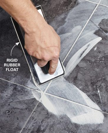 <b>Photo 12: Spread the grout</b></br> <p>To lessen the mess, use the narrow end of a rigid rubber float to work the grout into the joints. Scrape off the excess in a 45-degree motion.</p>