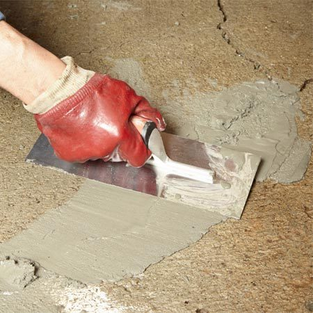 <b>Photo 4: Fill cracks, craters, divots and pits</b></br> Mix up a stiff batch of resurfacer, using just enough water for a workable consistency. Scrape off the excess so repairs are flush with the surrounding floor.