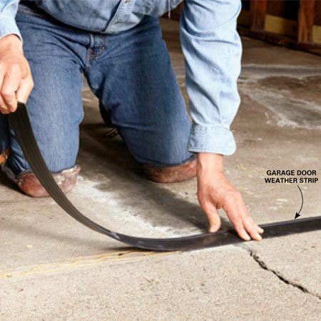 <b>Photo 5: Create a dam</b></br> Glue weather strip to the floor exactly where the garage door rests. This will stop resurfacer from flowing onto the driveway.