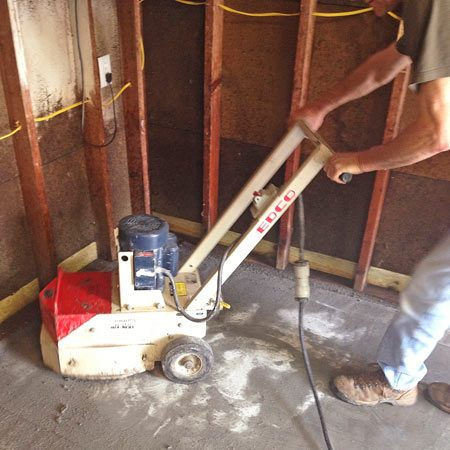 Concrtete grinder being used during garage floor resurfacing.