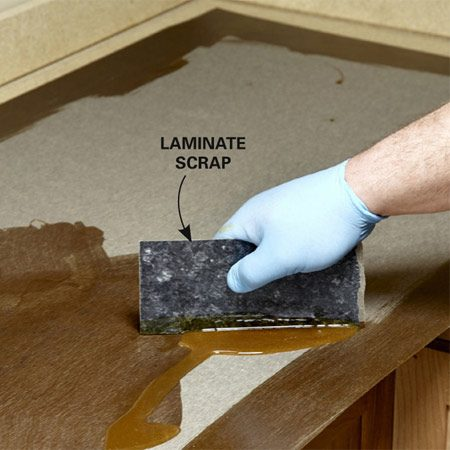 <b>Glue-up tip</b><br/>Clean all surfaces with compressed air before gluing up the top surface. Jamey covers the perimeter with a brush and then grabs a scrap piece of laminate to spread on the rest. Apply the glue on the underlayment the same way. It gets messy trying to glue the backsplash after the top is installed, so cover the backsplash with glue at the same time. And this stuff is a potent chemical, so always use an organic vapor respirator, open a window and turn on the exhaust fan.