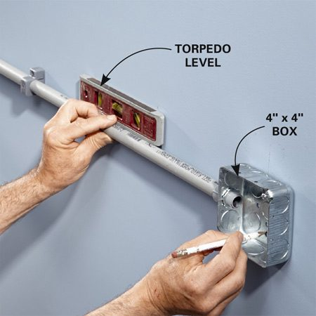 <b>Photo 6: Mount the next box</b></br> <p>Extend the piece of conduit between the two boxes. Hold it level and mark two holes in the back of the second box. Remove the box and install drywall anchors so you can mount the box to the wall.</p>
