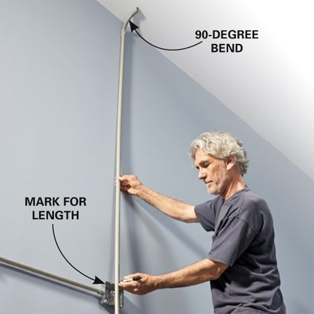 <b>Photo 7: Mark the vertical conduit</b></br> <p>Connect a 90-degree bend to the conduit. Hold it against the ceiling and mark the top edge of the electrical box on the conduit. Subtract 1/4 in. and cut the conduit.</p>