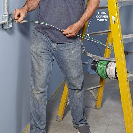 <b>Photo 8: Push wires into the conduit</b></br> <p>Hang the wire spools on a steel pipe or dowel so they can spin freely. Bend the ends of the wires over so they don''t catch on edges inside fittings, and then push them through the conduit.</p>