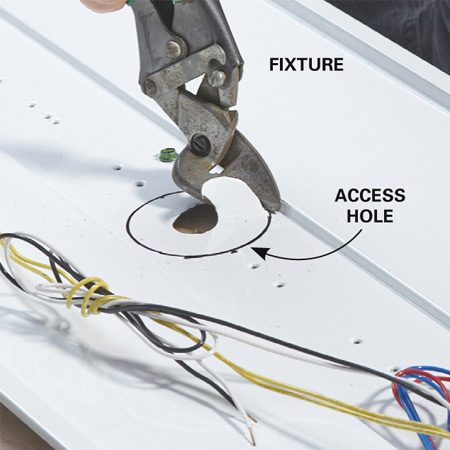 <b>Photo 10: Cut an access hole</b></br> <p>Start with a hole in the middle to get the snips started. Our fixture had a knockout that we removed. Otherwise, use a small hole saw to drill a starting hole. Snip out to the circle and follow it with the snips.</p>