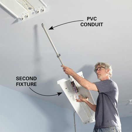 <b>Photo 11: Connect in-line fixtures</b></br> <p>Hang the second fixture with the conduit already attached. There's no easy way to insert straight runs of conduit between fixtures that are already fastened to the ceiling.</p>