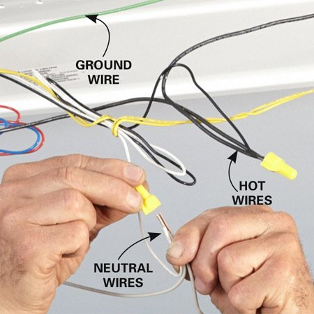 <b>Photo 14: Connect the fixture wires</b></br> <p>Strip the ends of the new wires and connect them to the wires in the fixture. Connect all neutral white wires together. Connect the colored fixture wire to the black wires.</p>