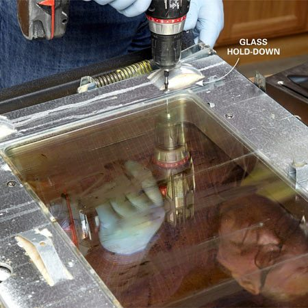 <b>Photo 2: Remove the glass</b></br> Remove the screws from the glass hold-downs and set them aside. Note the location of the retaining tabs above and below the glass. Then lift off the glass and clean it.
