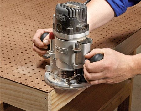 <b>Photo 2: Trim the pegboard flush</b></br> Install a flush-trim bit in your router and trim off the overhanging pegboard. Routing pegboard whips up a dust storm, so wear a mask.