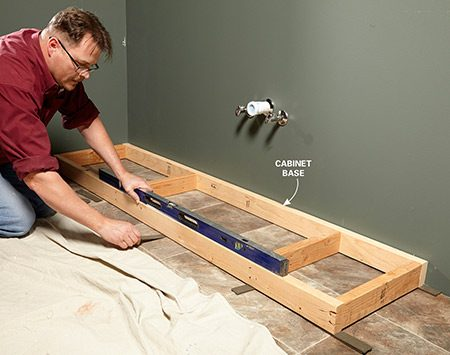 <b>Level the base</b></br> <p>It's important to use dead-straight wood for bases so it'll be flat for setting the cabinets. Once your cabinets are installed, finish off the base front with a strip of 1/4-in. plywood that matches the cabinets.</p>