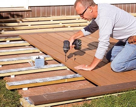 <b>Photo 4: Lay the decking</b></br> <p>Install the deck boards just as you would on a standard deck. When you reach the end of the patio, position the last board, mark the overhanging sleepers and trim off the excess.</p>