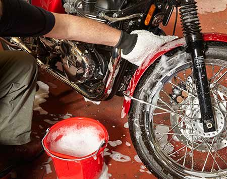 <b>Photo 1: Prewash with a damp mitt and suds</b></br> <p>Dip the mitt into soapy water and wring out the excess. Then wipe the damp mitt over the entire bike. Avoid soaking the dash gauges, buttons and switches.</p>