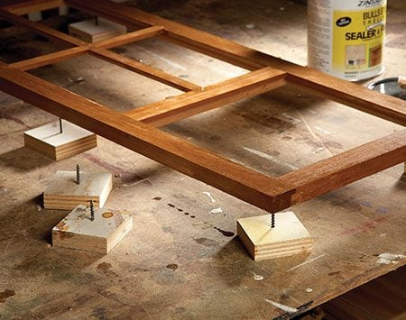 <b>Finish both sides at once</b></br> <p>Screw screws through pieces of scrap wood to make finishing stands.</p>