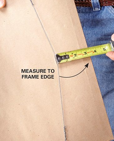<b>Photo 1: Measure from the wire</b><br/><p>Measure the distance from the stretched wire to the top of the picture frame.</p>