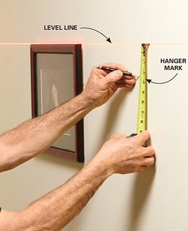 <b>Photo 2: Mark for the picture hanger</b></br> <p>Measure down from the level line and mark for the location of the picture-hanging hook.</p>
