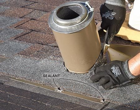 <b>Photo 14: Shingle over the vent flashing</b><br/><p>Seal the nail heads, and trim around the stack flashing with a utility knife fitted with hook blades.</p>