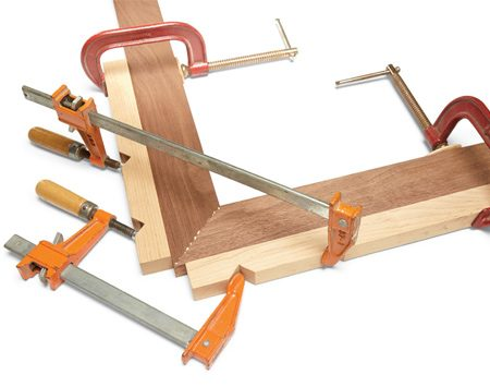 <b>Put extra pressure on miter joints</b><br/><p>This is an old favorite among woodworkers: Clamp on notched blocks, then add a bar clamp or two to squeeze the joint. This allows you to put a lot of pressure on the joint without buying any special clamps. If you&rsquo;re assembling a four-sided project such as a picture frame, join two corners first. Then, after the glue has set, join the two halves of the frame.</p>