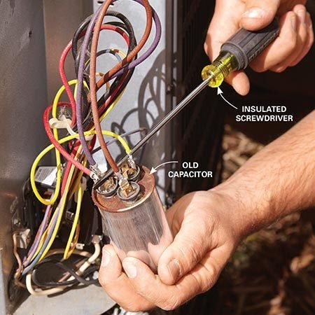 "<b>Photo 4: Discharging a dual start/run capacitor</b></br> <p>Remove the capacitor from the retaining bracket. Then touch an insulated screwdriver between the HERM (or ""H"") terminal and the COMMON (or ""C"") terminal. Do the same between the FAN (or ""F"") terminal and the ""C"" terminal. On single-mode capacitors, just make a short between the two terminals.</p>"