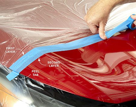 <b>Photo 1: Tape the poly sheeting to the hood</b></br> <p>Carefully apply the first layer and then the second layer directly below it. Make the second tape line as straight as possible, and press down along the edge to seal it to the hood as you apply. Double over one end of the tape to make a peel tab.</p>