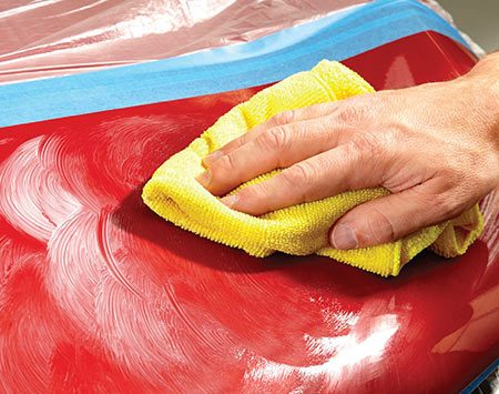 <b>Photo 2: Wax the exposed hood area</b></br> <p>Squirt a dollop of wax onto the hood and work it in with a microfiber towel. Continue wiping until the surface is free of haze.</p>