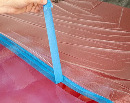 <b>Photo 4: Remove the tape while the spray is wet</b></br> <p>Grab the doubled-over peel tab and pull the clean-edge tape up and away from the wet edge.</p>
