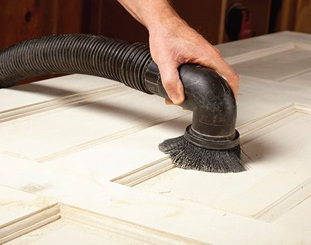 <b>Photo 3: Remove the sanding dust</b></br> <p>A vacuum with a brush attachment removes most of the dust. Wipe off the rest with a damp rag.</p>