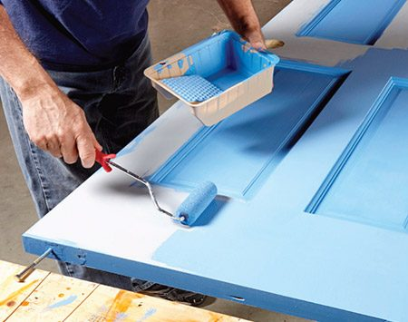 <b>Photo 8: Roll the rails and stiles</b></br> <p>Roll the door in sections, coating no more than one-quarter of the door at a time. Then brush out the paint. Be careful not to slop paint over the edges around the panels.</p>