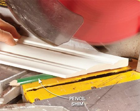 """<b>Solution:  Cut a """"back bevel""""</b></br> <p>You could tilt the saw blade to back-bevel the  miters, but   tilting  the trim is faster and easier. Slip a pencil or shim   under the  molding, just behind where the cut will be. Cut   both  sides of the miter with shims in the same position. Then test the fit and make adjustments as needed. </p>"""