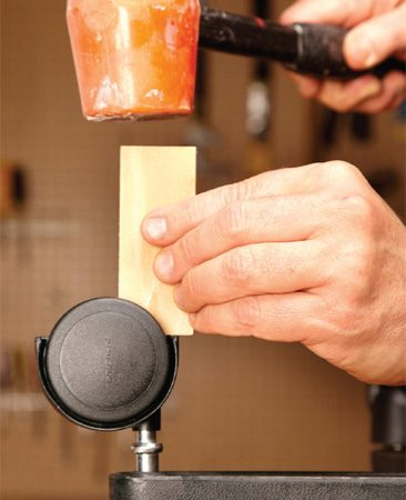 <b>Photo 3: Tap it in</b></br> <p>Position a small block of wood directly over the caster stem. Then tap it with a mallet until the stem pops all the way into the socket.  </p>