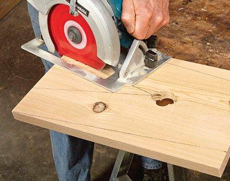 "<b>Photo 3: Cut the leg angles</b></br> <p>Mark the ""V"" in the center and the two outside angles on the legs. Then cut along the lines with a circular saw. Accurate cutting is easier if you clamp the leg to the workbench.</p>"