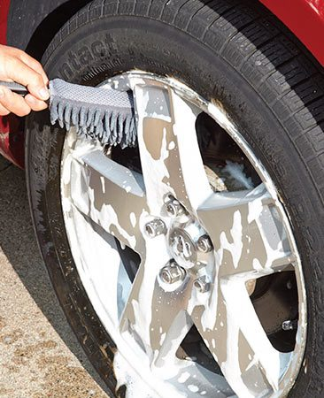 <b>Scrub the wheels</b><br/><p>Spray the wheels with an aluminum-safe alloy wheel cleaner and scrub with a wheel-cleaning brush. Rinse the wheels and clean any areas you missed. Then do a final wheel rinse.</p>