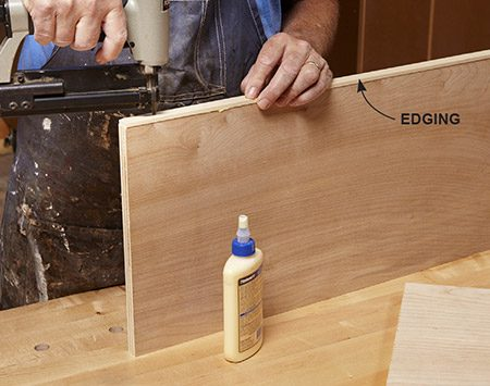 "<b>Photo 2: Tack on the edging</b></br> <p>Spread a little glue and tack the edging onto the plywood parts with a pinner or brad nailer. Center the edging by ""feel,"" allowing it to overhang slightly on both sides. The edging can also overhang the plywood at one end. But the other end should be flush with the plywood.</p>"