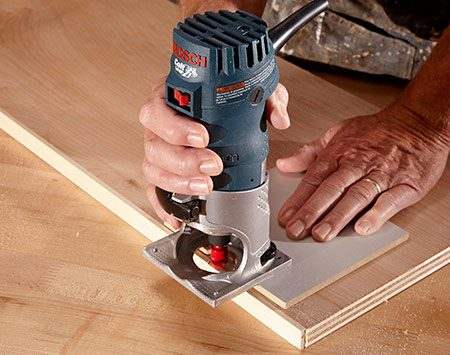 <b>Photo 4: Trim the edging flush</b></br> <p>A straight router bit set at just the right depth will trim off the protruding edging without cutting into the plywood.</p>