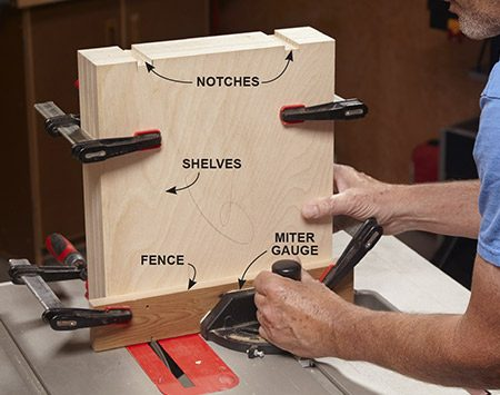<b>Photo 7: Notch the shelves</b></br> <p>Notches fit over the shelf supports and prevent the shelves from slipping out of the cabinet. To cut notches, mount a fence on your miter gauge and clamp the shelves to it. Make several passes to complete each notch.</p>