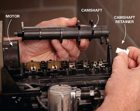 <b>Photo 1: Remove the camshaft</b></br> <p>Unscrew the cam lock or rotate the cam lock lever and lift up on the rear end of the camshaft. Pull it out of the motor and set it aside.</p>