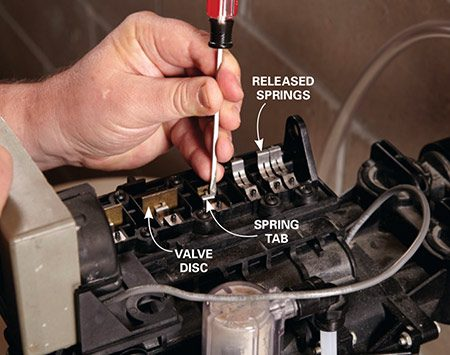<b>Photo 2: Disengage the springs</b></br> <p>Slide a small flat-blade screwdriver under the spring and pry the tab out of the valve disc. Then pop the spring up.</p>