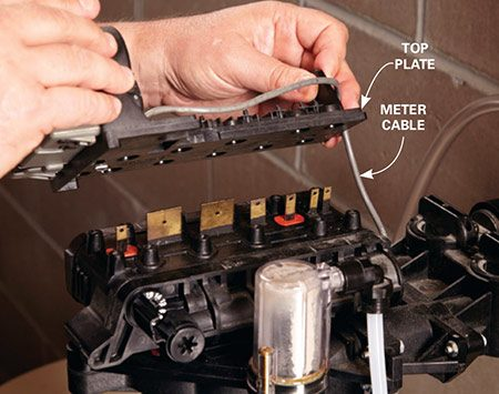 <b>Photo 3: Remove top plate</b></br> <p>Unscrew 12 retaining screws. Then lift the top plate straight up. Disengage the meter cable (if equipped) and set the plate on top of the bypass valves.</p>
