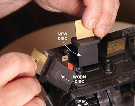 <b>Photo 4: Install new valve discs</b></br> <p>Yank the old valve discs straight up. Then insert the matching replacement discs (no lube needed). Press the rubber portion of each disc into the valve body until it's flush.</p>