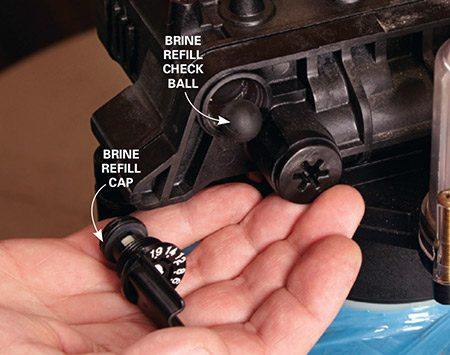 <b>Photo 6: Replace the brine refill check ball</b></br> <p>Grab the brine refill control cap with pliers and unscrew. Smack the control head with the palm of your hand to knock out the rubber check ball. Clean any debris and install the new check ball. Reinstall the control cap.</p>