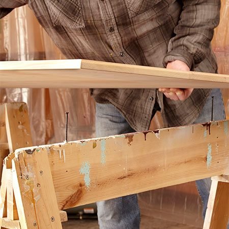 <b>Prop up the tabletop</b></br> <p>Set the top on screws so you can easily finish the edges.</p>