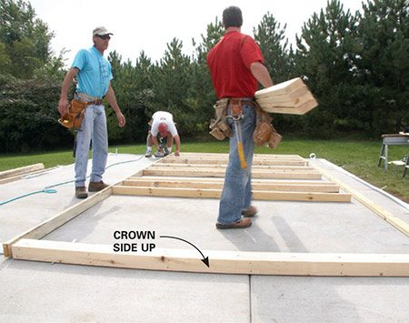 "<b>Photo 3: Assemble the walls</b></br> <p>To avoid a wavy wall, sight down each stud to determine which way it's ""crowned"" (bowed) and then position them all with the crown facing up so they don't act like a rocking chair. Have one crew member haul the studs, one line them up and one nail them.</p>"
