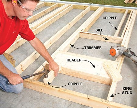 <b>Photo 4: Build the window and door openings</b></br> <p>Assemble a window opening in this order: king studs, header, trimmer, lower cripples, windowsill, upper cripples. Don't cut out the plate that spans the bottom of a door opening until the wall is set. The last step is nailing on the top plates.</li>