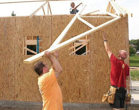 <b>Photo 12: Heave up the rest of the trusses</b></br> <p>It's easier to slide trusses up on their side. In order to maintain the room to accomplish that, haul up the rest of the trusses and lean them against the end or center truss.</p>