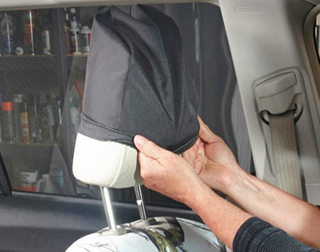 <b>Photo 6: Install the headrest covers</b></br> <p>Stretch the elastic edges around the headrest and pull it down. Tug at the cover fabric until it fits smoothly on the contour of the headrest.</p>