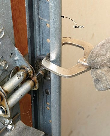 <b>Clamp the door to the track</b></br> <p>Clamp a locking pliers or a C-clamp to the track just above one of the rollers. This will prevent the door from shooting up and breaking your nose when you wind the new springs. Also yank the cord and unplug the garage door opener.</p>