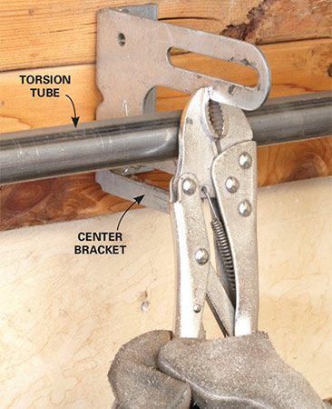<b>Use locking pliers</b></br> <p>Snap a locking pliers or a C-clamp onto the center bracket to hold the torsion tube in the bracket. Then loosen the setscrews on the left and right lift cable drums and disconnect the lift cables.</p>