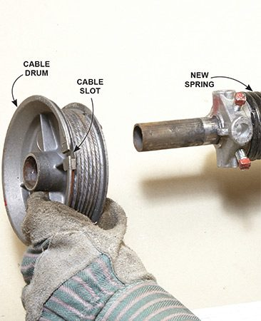 <b>Reassemble, then hang on the bearing bracket</b></br> <p>Slide the new spring onto the torsion tube with the stationary cone facing the center bracket. Then reinstall the cable drum. Reinsert the torsion bar into the left-side bearing bracket.</p>